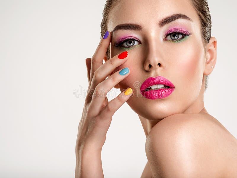 Mooie maniervrouw met gekleurde spijkers Aantrekkelijk wit meisje met veelkleurige manicure stock afbeelding