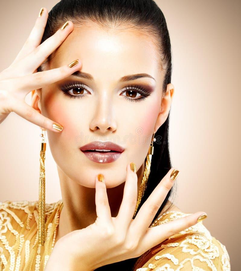 Mooie maniervrouw met zwarte make-up en gouden manicure stock afbeelding