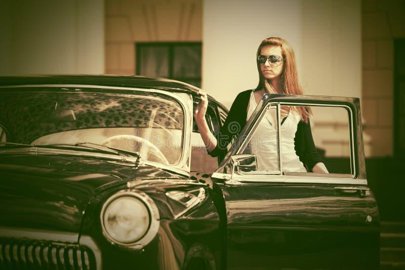Mooie maniervrouw naast retro auto stock afbeelding