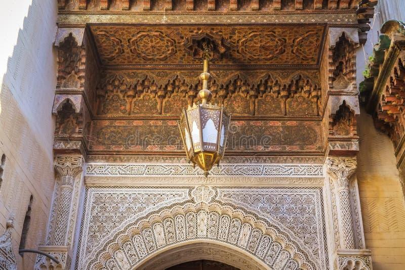Mooie Marokkaanse kunst in de stad van Fez Houten gesneden plafond, antieke lamp en arabesque kunst op de muur marokko stock afbeelding