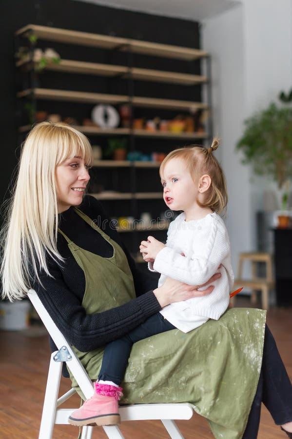 Mooie mededeling van moeder en weinig dochter in een creatieve workshop De dag van moeders stock foto's
