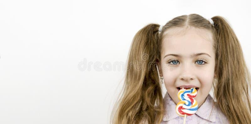 Mooie meid met blauwe ogen die lolly eet, geïsoleerd op wit stock foto