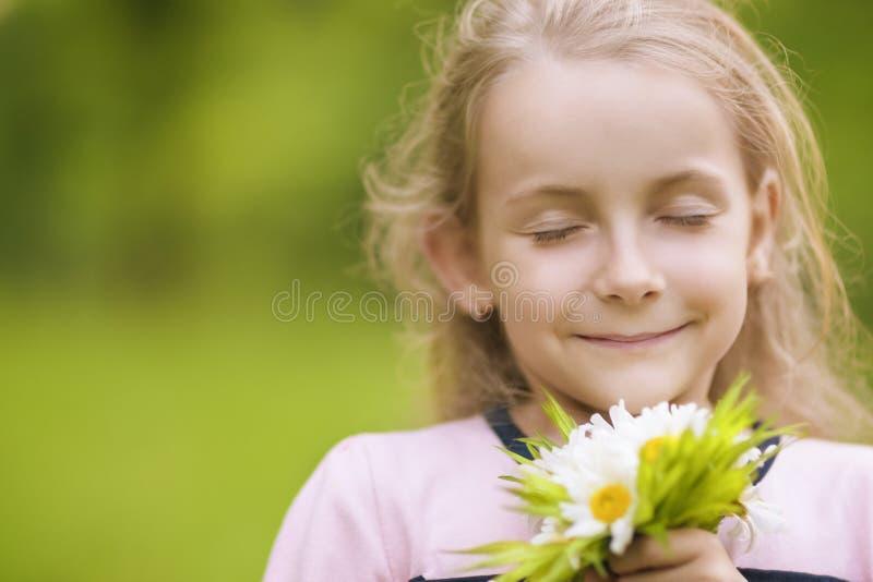 Mooie meisje ademhalingsbloemen royalty-vrije stock foto