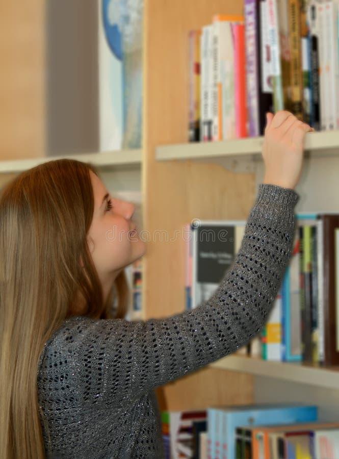 Mooie meisje het doorbladeren boekenrekken royalty-vrije stock afbeeldingen
