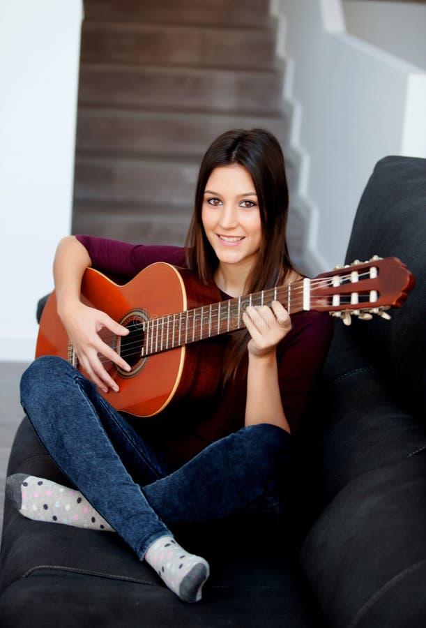 Mooie meisje het spelen gitaar op de laag royalty-vrije stock foto