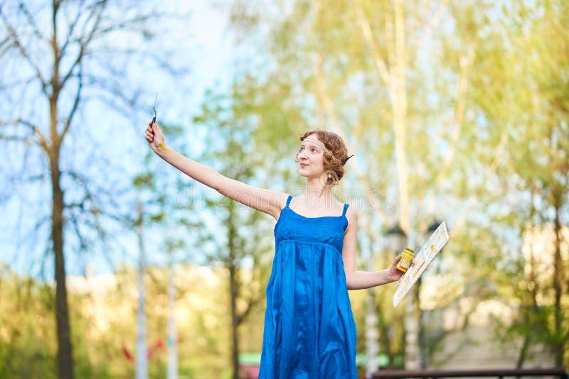 Mooie meisje-kunstenaar op de straat in een blauwe kleding, die met leeswijzers en palet in haar handen glimlachen royalty-vrije stock afbeelding