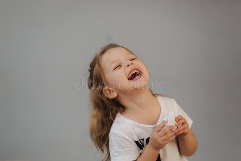Mooie meisjeglimlach aan camera Grijze achtergrond wij zijn alle jonge geitjes stock afbeeldingen