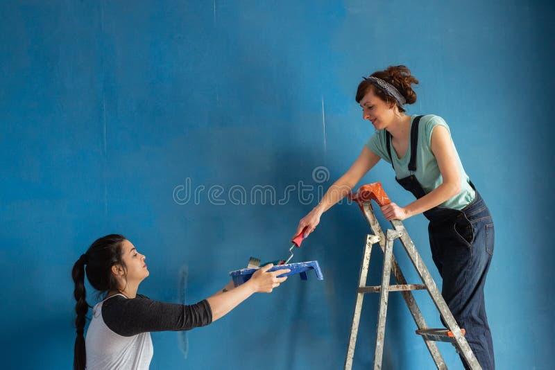 Mooie Meisjes die de Blauwe Muur schilderen royalty-vrije stock foto's