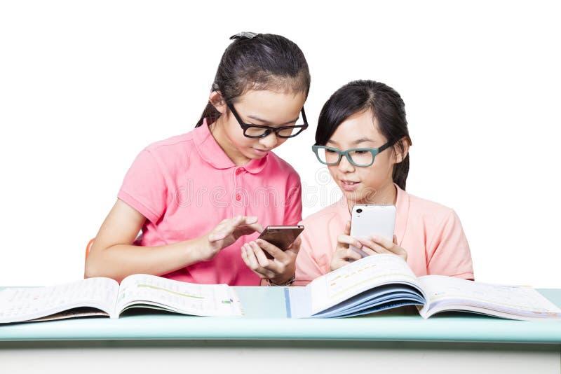 Mooie meisjes die mobiele telefoon in klaslokaal met behulp van stock afbeelding