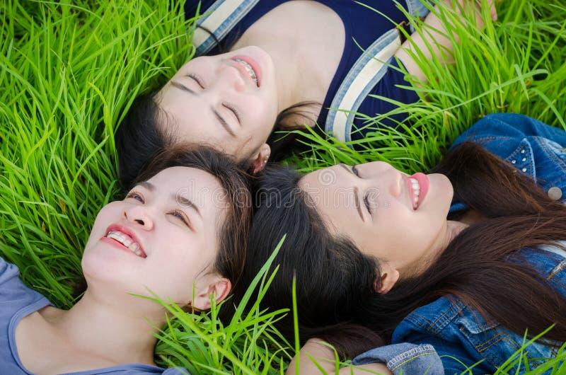 Mooie meisjes die op grasgebied liggen royalty-vrije stock afbeeldingen