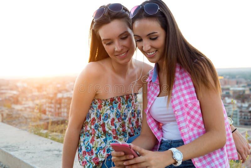 Mooie meisjes die op het dak zitten en aan muziek bij su luisteren stock afbeelding
