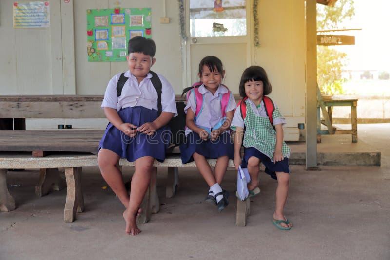 3 mooie meisjes die op plattelandsgebied eenvormige school dragen, schooltas Zit op de houten stoel en het glimlachen met vreugde stock fotografie
