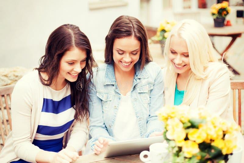 Mooie meisjes die tabletpc bekijken in koffie stock foto's