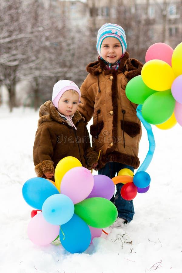 Mooie meisjes met ballons in de winter royalty-vrije stock foto's