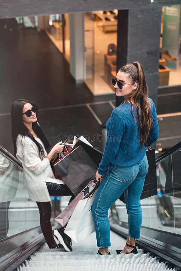 Mooie meisjes met document zakken op roltrap bij supermarkt royalty-vrije stock afbeeldingen