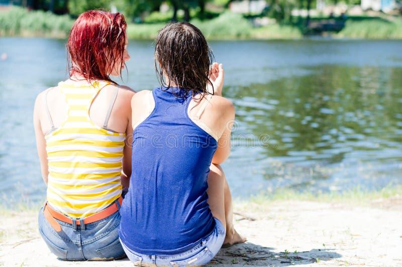 2 mooie meisjes in natte kledingsoverhemden die pret ontspannende zitting op de bank van de rivier op zandig strand hebben stock foto