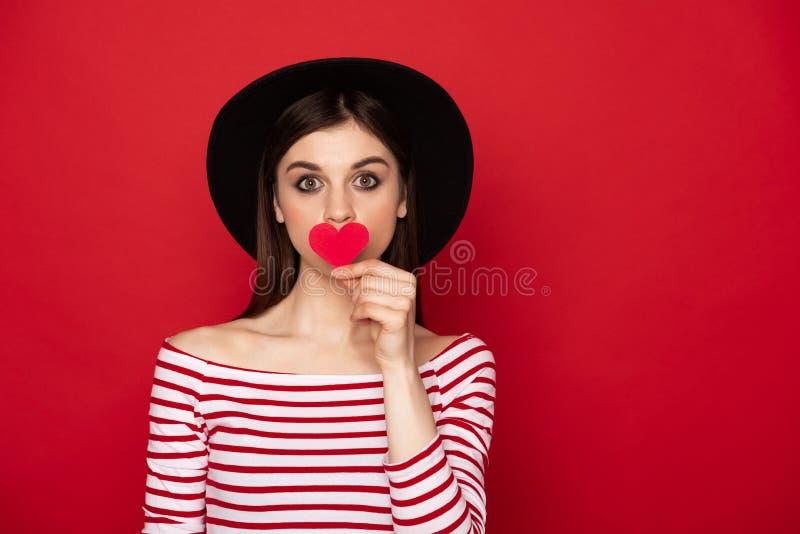 Mooie meisjes sluitende lippen door rood document hart stock fotografie