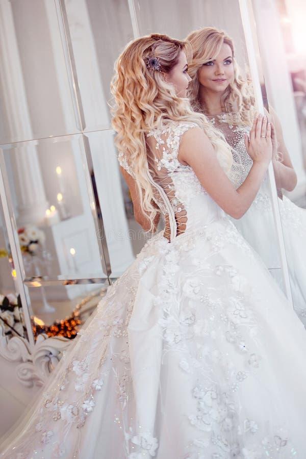 Mooie meisjesbruid in een prachtige kleding Luxueus licht binnenland royalty-vrije stock foto