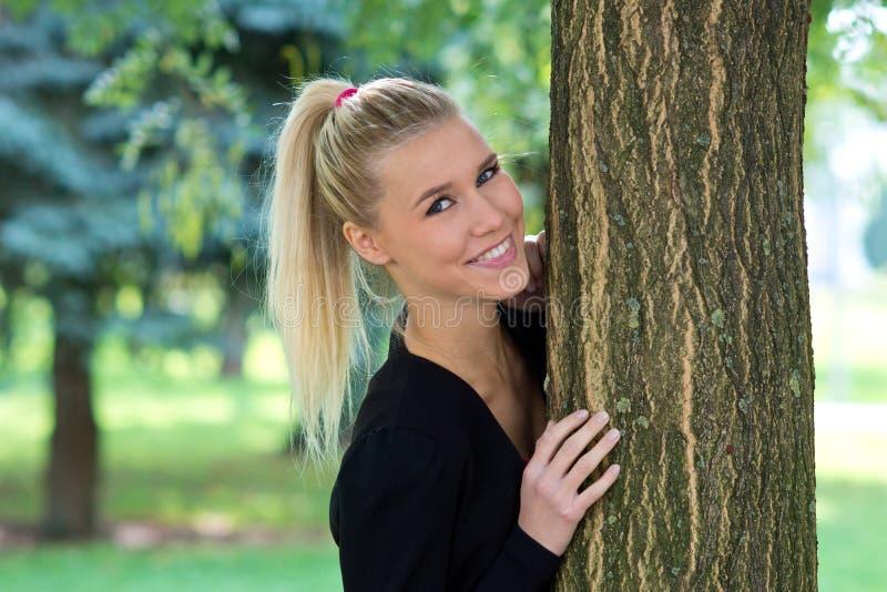 Mooie meisjesbuitenkant netx aan boom stock afbeelding