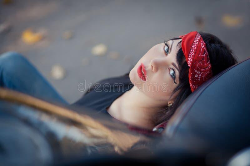 Mooie meisjesfietser of leuke vrouw met modieus, lang haar die jeans dragen die op vloer bij motorfiets zitten royalty-vrije stock foto's
