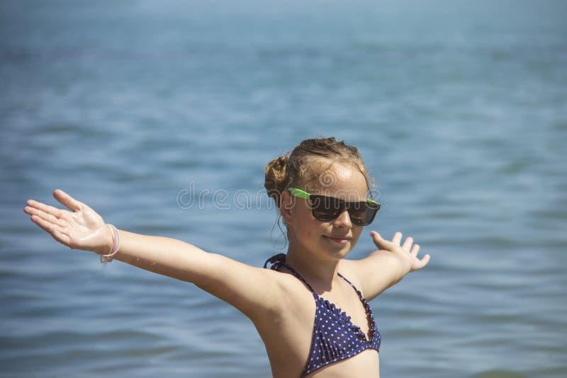 Mooie meisjesglimlach met opgeheven handen, vrouw op de vakantie van de strandzomer concept vrijheidsreis royalty-vrije stock fotografie