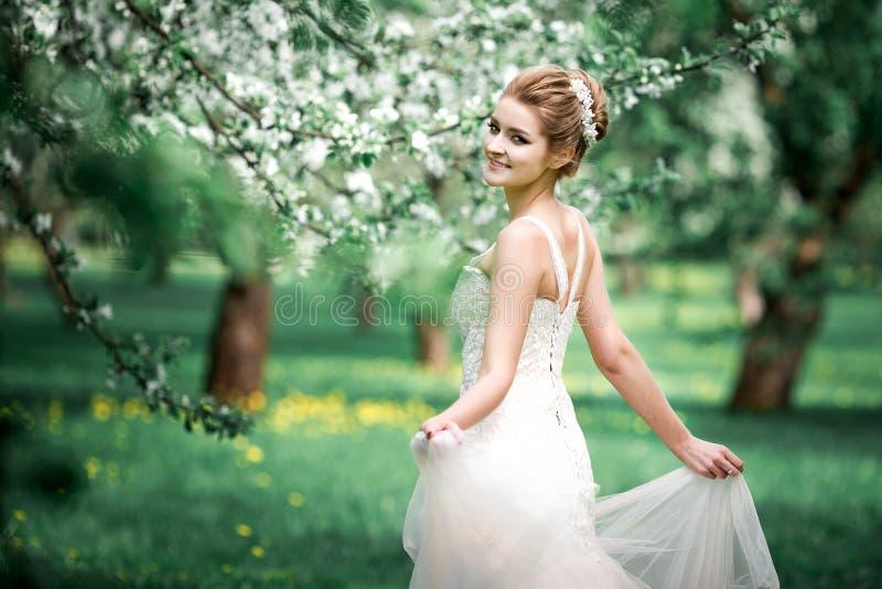 Mooie meisjeshanden met een tak van een tot bloei komende appelboom Jonge mooie blondevrouw in bloeiende tuin royalty-vrije stock foto's