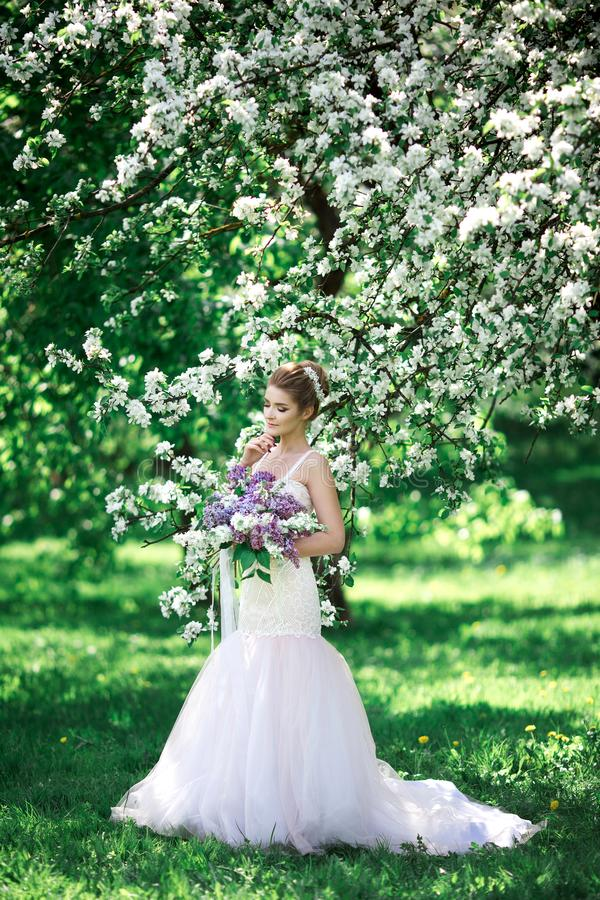 Mooie meisjeshanden met een tak van een tot bloei komende appelboom Jonge mooie blondevrouw in bloeiende tuin stock foto