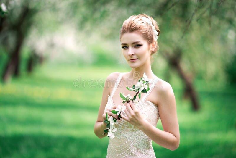 Mooie meisjeshanden met een tak van een tot bloei komende appelboom Jonge mooie blondevrouw in bloeiende tuin stock fotografie