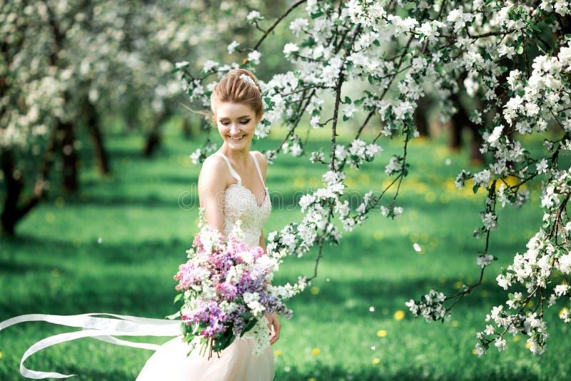 Mooie meisjeshanden met een tak van een tot bloei komende appelboom Jonge mooie blondevrouw in bloeiende tuin stock foto's