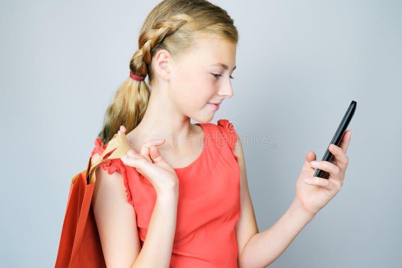 Mooie meisjesholding het winkelen zak en het bekijken mobiele telefoon stock fotografie
