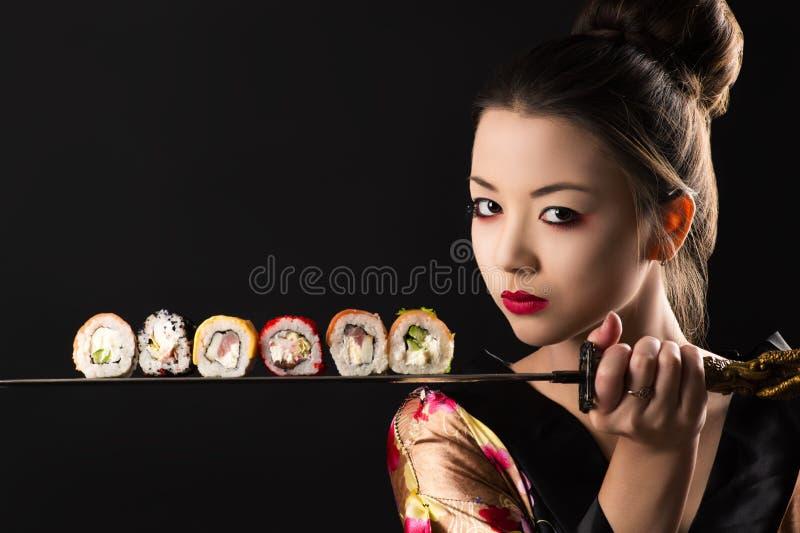 Mooie meisjessamoeraien met zwaard en broodjes stock foto's