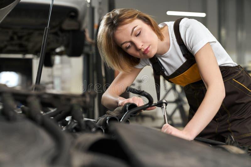 Mooie meisjeswerktuigkundige in het eenvormige herstellen, het bevestigen auto royalty-vrije stock afbeeldingen