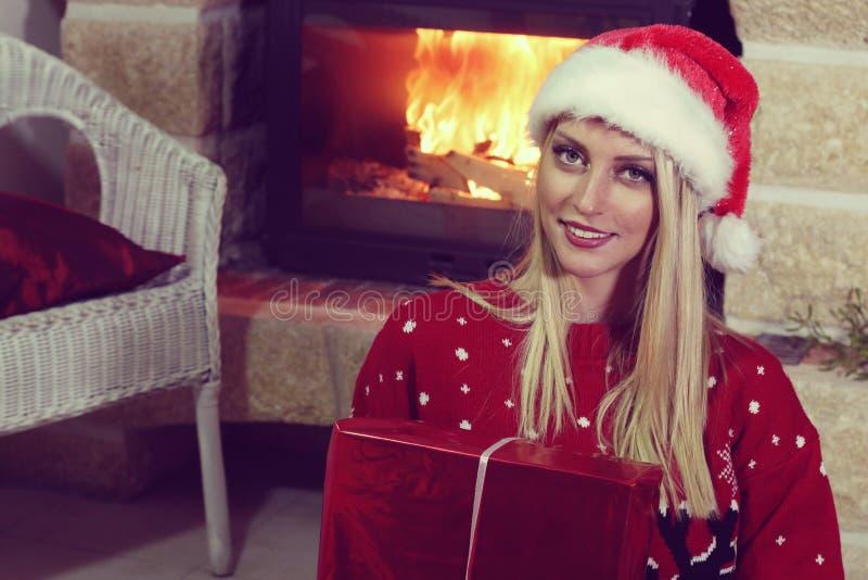 Mooie meisjeszitting naast een open haard voor Kerstmis royalty-vrije stock foto