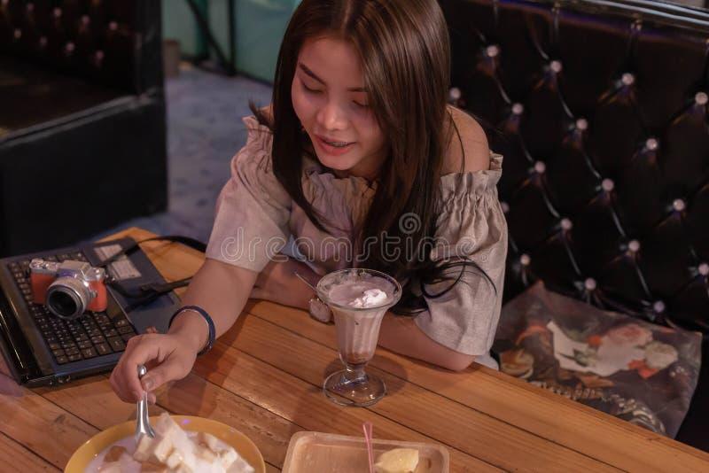Mooie meisjeszitting om roomijs in de winkel te eten stock foto