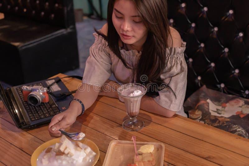 Mooie meisjeszitting om roomijs in de winkel te eten stock afbeelding