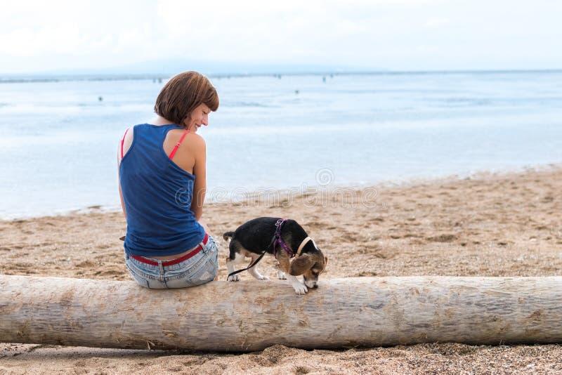 Mooie meisjeszitting op het strand met een puppy van de brakhond Tropisch eiland Bali, Indonesië stock afbeeldingen