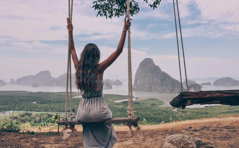 Mooie meisjeszitting op schommeling op de bovenkant van heuvel met fantast royalty-vrije stock fotografie