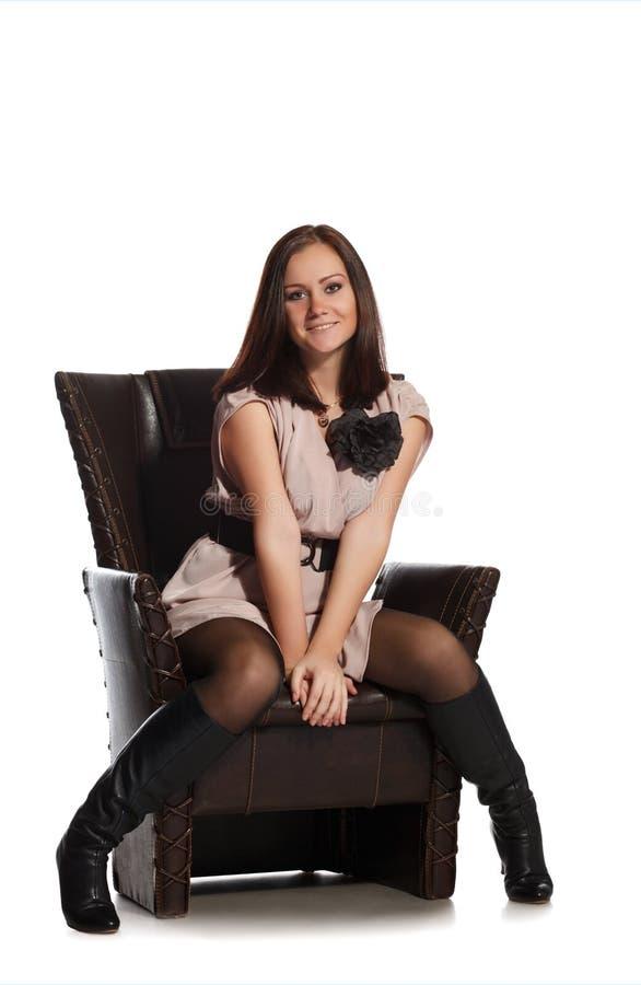 Mooie meisjeszitting op stoel stock fotografie