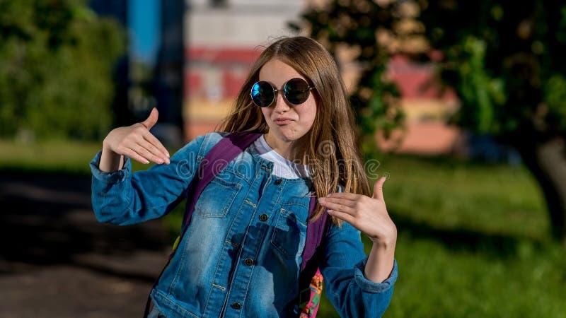 Mooie meisjetiener in jeanskleren in de zomer in de stad Het concept is een koel modieus meisje, royalty-vrije stock fotografie