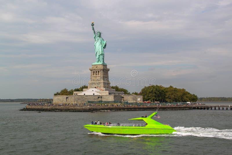 Mooie mening die van groene motorboot door beroemd Standbeeld van Vrijheid overgaan royalty-vrije stock afbeeldingen
