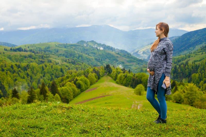 Mooie mening van berg met zwangere vrouw op foregrou stock fotografie