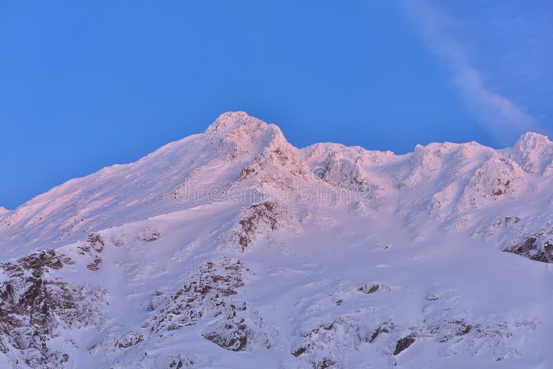 Mooie mening van bergpiek met zonsonderganglicht op bovenkant tegen royalty-vrije stock afbeeldingen