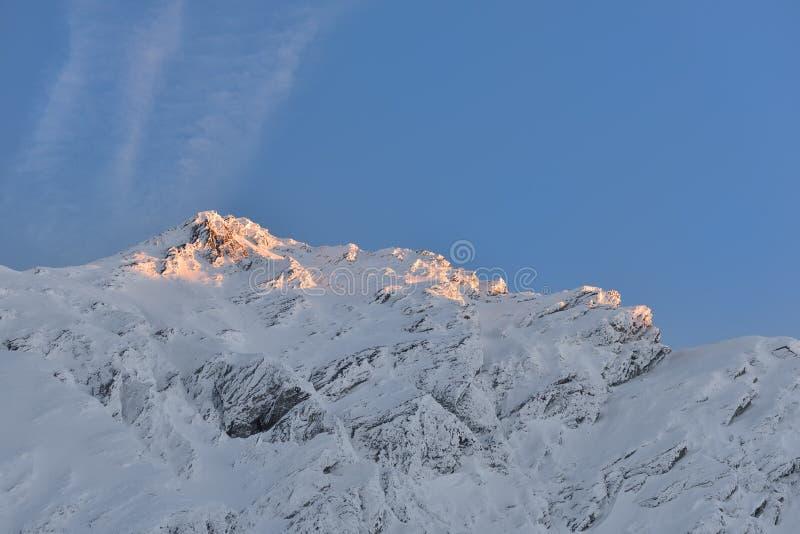 Mooie mening van bergpiek met zonsonderganglicht op bovenkant tegen stock fotografie