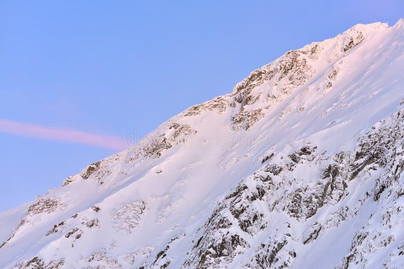 Mooie mening van bergpiek met zonsonderganglicht op bovenkant tegen royalty-vrije stock foto's