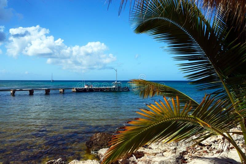 Mooie mening van de Caraïbische Zee, het blauwe overzees, een gebroken brug en een boot van een zandig strand met blauwe stoelen  stock foto