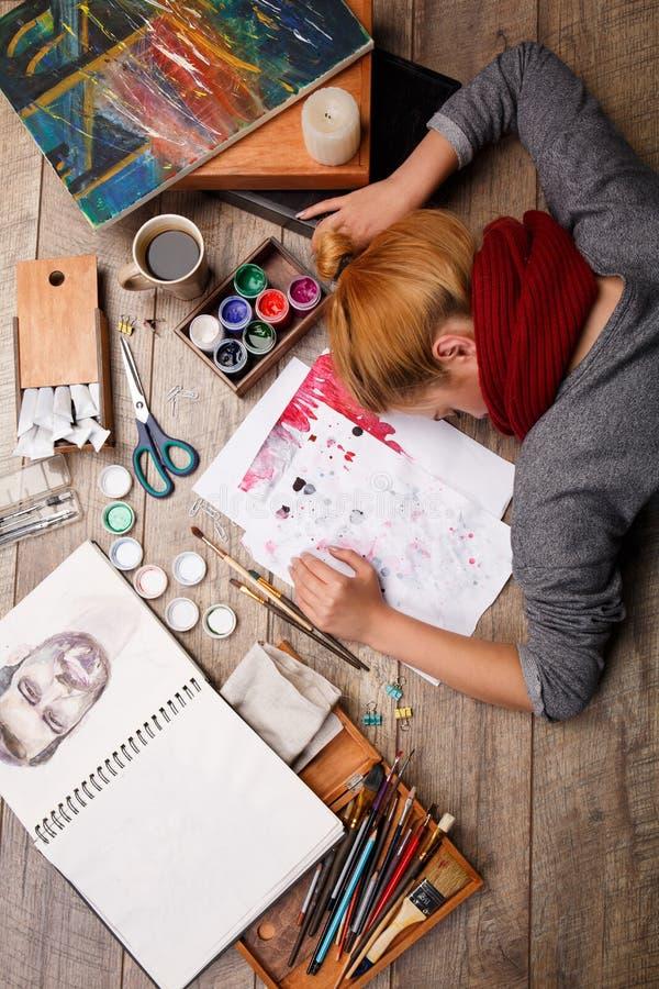 Mooie mening van de kunstenaar en de voorwerpen voor het schilderen op houten parket Het concept van de kunst Wit masker met rode royalty-vrije stock fotografie