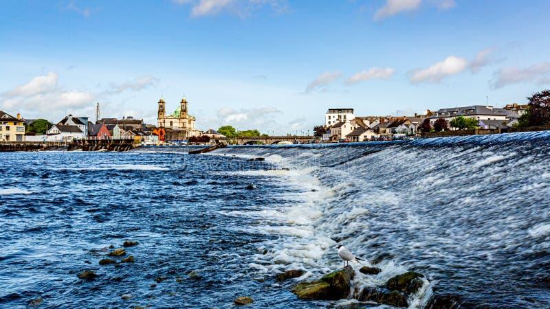 Mooie mening van de rivier Shannon met de parochiekerk van Ss Peter en Paul, hun brug in het dorp van Athlone stock foto's