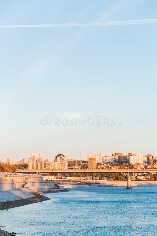 Mooie mening van de stad over de blauwe brede rivier met een brug Een lang gebouw royalty-vrije stock foto's