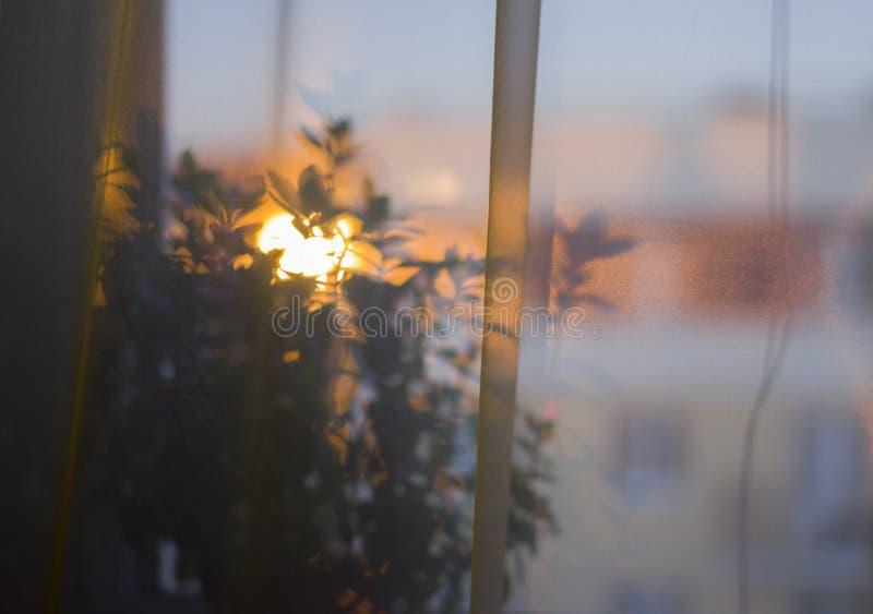 Mooie mening van de zonsondergang op de vage mening van het venster stock foto