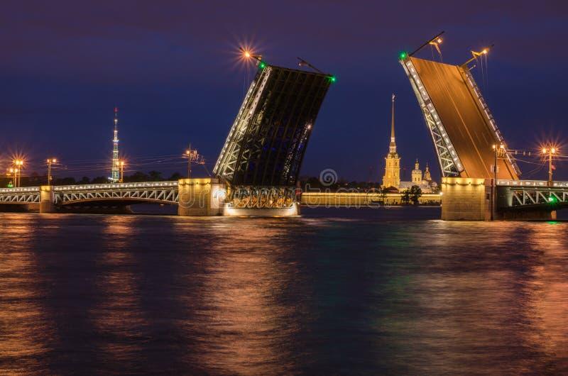 Mooie mening van het fokken van bruggen in nachtst. petersburg van de dijk van Neva River royalty-vrije stock afbeelding